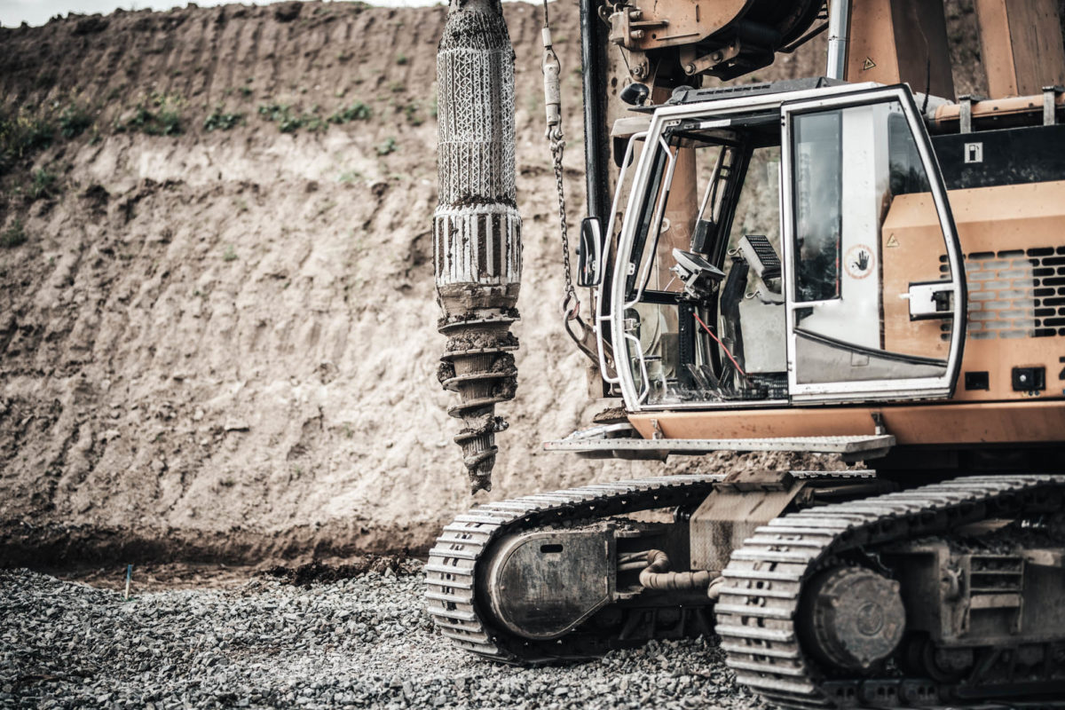Construction site, highway building with industrial rotary drilling machinery close up