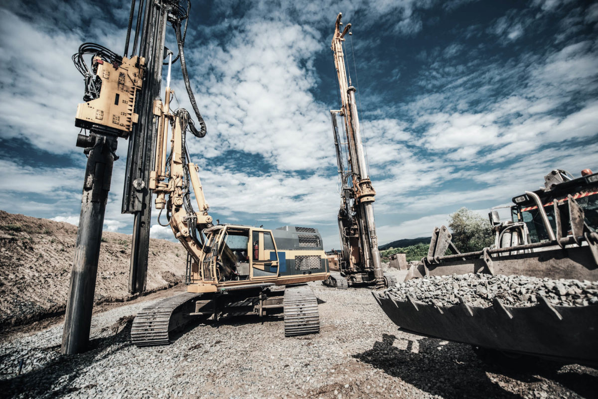 Highway construction site with heavy duty machinery. Two Rotary drills, bulldozer and excavator working